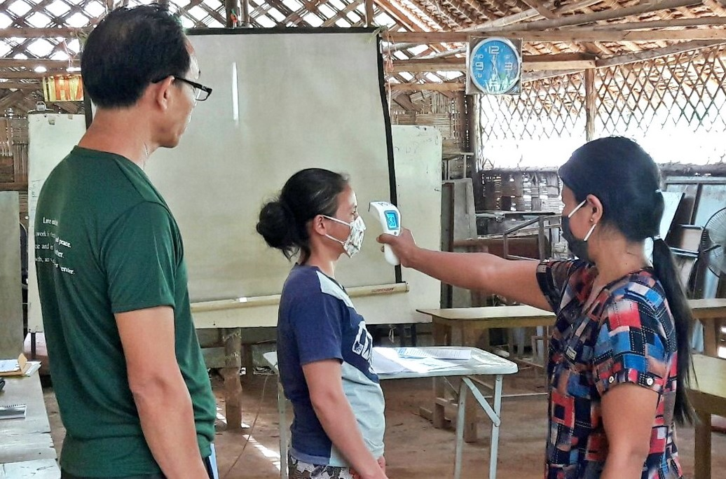 Head teacher training on how to use Infrared thermometer and mask for Covid-19 prevention to prepare for school re-opening and pilot class in Ban Mai Nai Soi temporary shelter on 28 May 2020. (JRS AP)